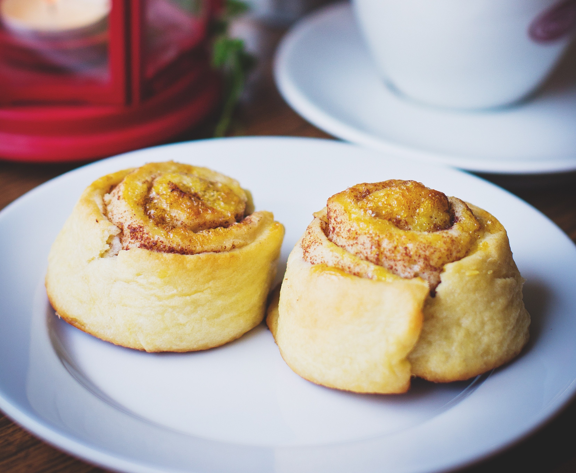 Two cinnamon buns on a plate in the foreground with cup of cappuccino and holiday styled lanterns in the background.